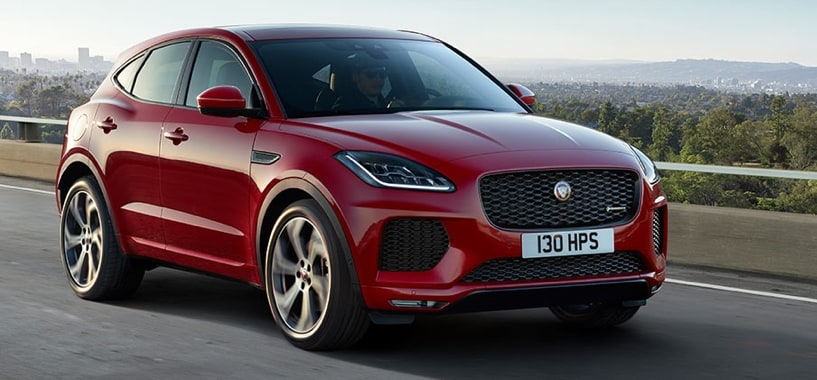 A Red Jaguar E-Pace Driving on a hill-top road