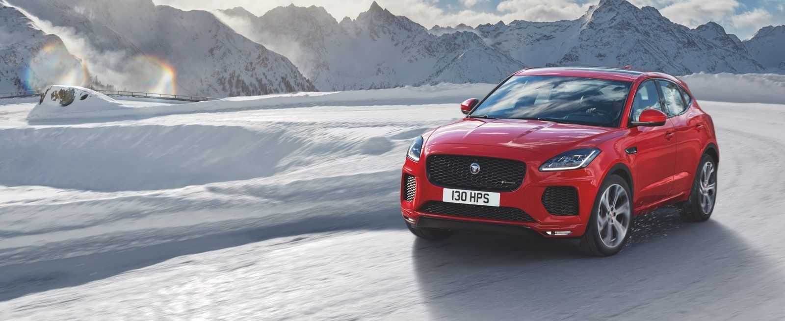 A Red Jaguar E-Pace Driving Driving on a Snow Covered Road