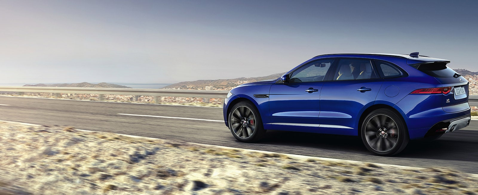 Blue Jaguar F-Pace Driving Along A Desert Road