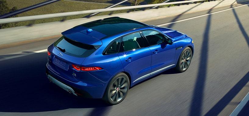 Blue Jaguar F-Pace Driving Across A Bridge