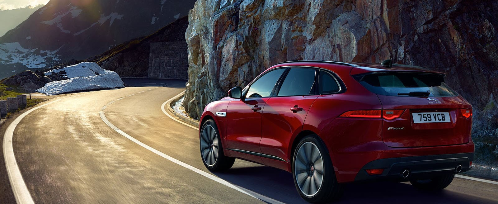 Red F-Pace Driving Along a Mountainous Road