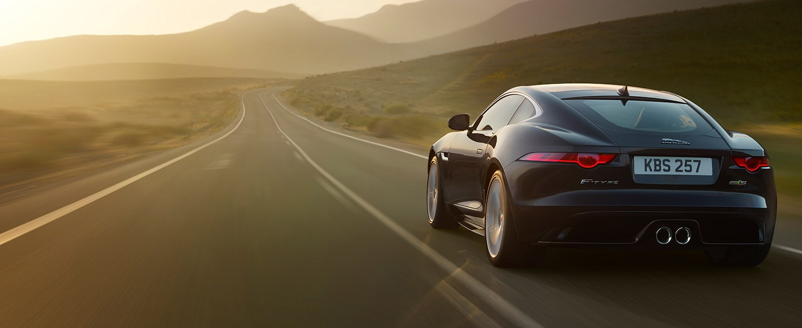 A Black Jaguar F-Type Driving Down A Desert Road