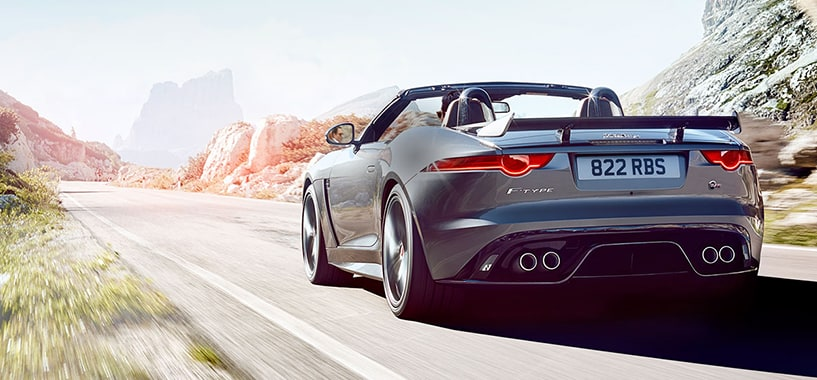 A Grey Jaguar F-Type Driving on A Desert Road With The Convertible Roof Down