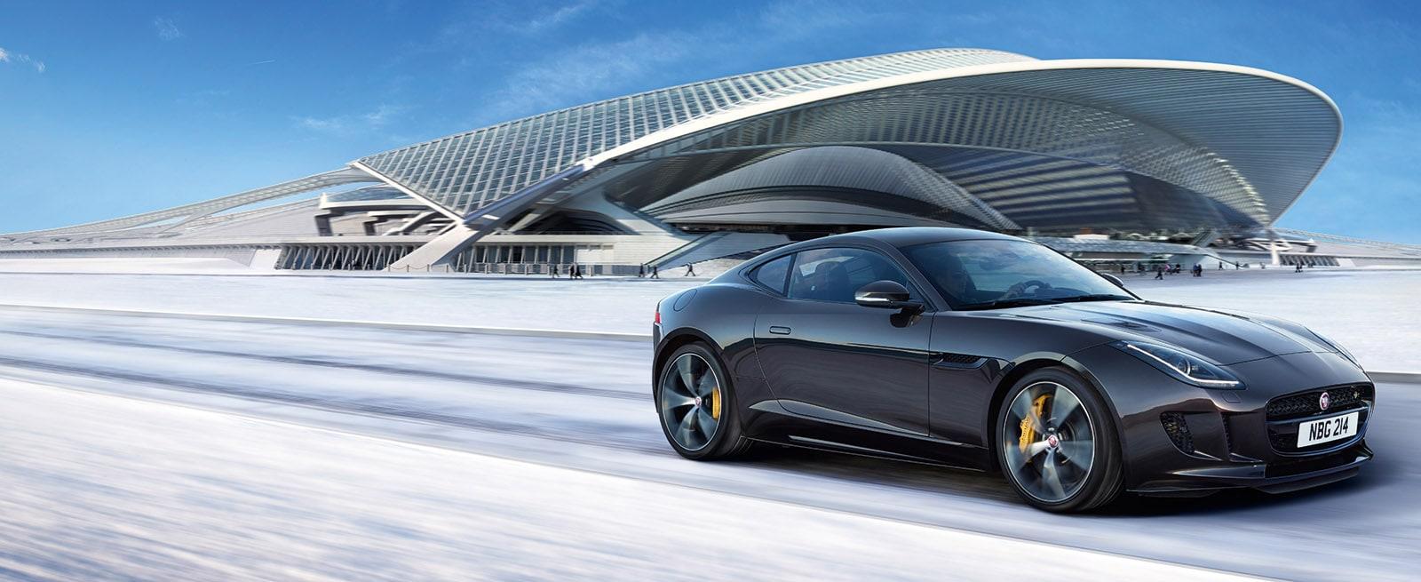 A Grey Jaguar F-Type Racing Down a Snowy Track