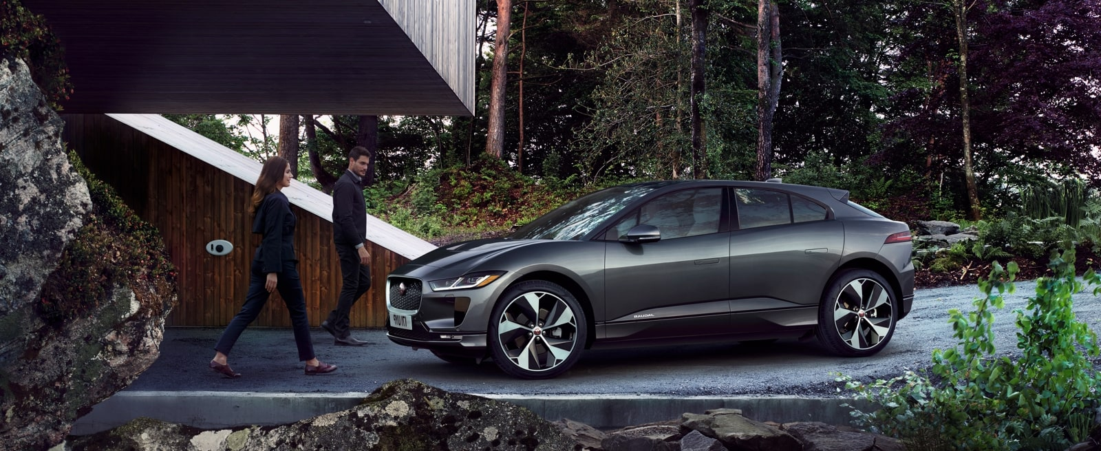 A Grey Jaguar I-Pace Parked in Front of a Modern Woodland House