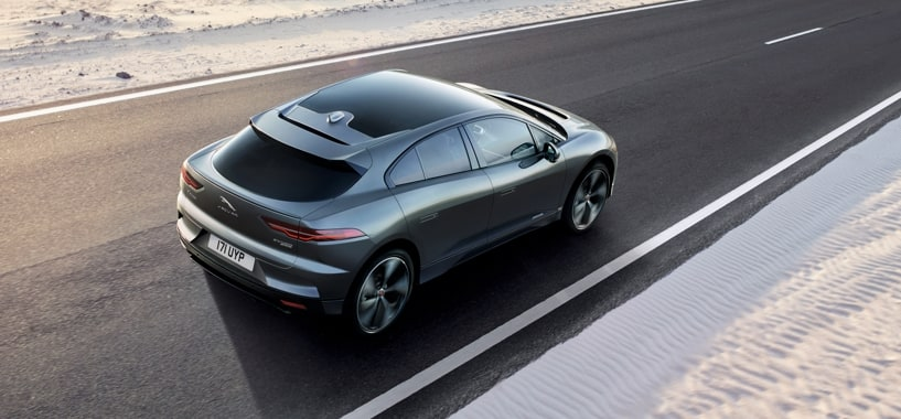 A Silver Jaguar I-Pace Driving Through A Snowy Climate