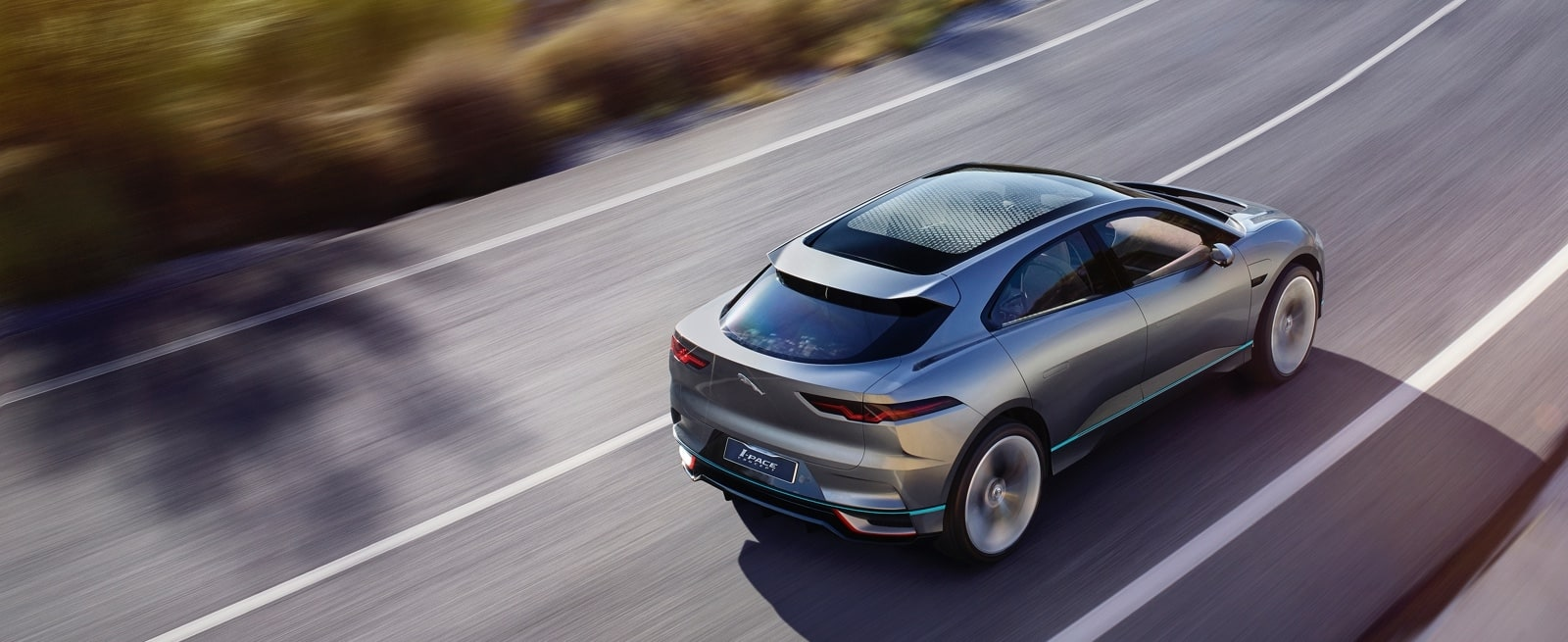 A Silver Jaguar I-Pace Driving Quickly