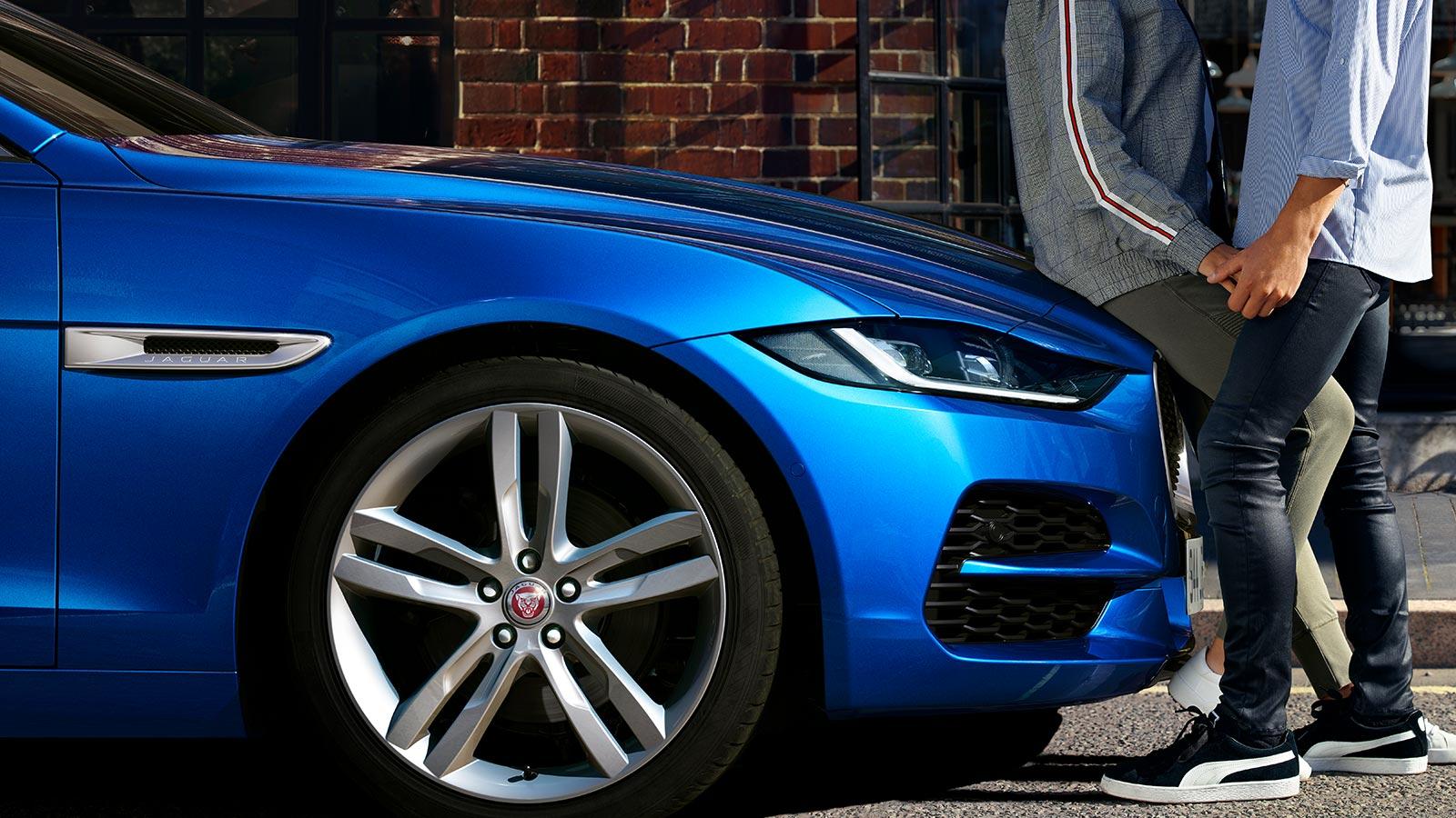 A Couple Leaning on the Bonnet of A Blue Jaguar XE