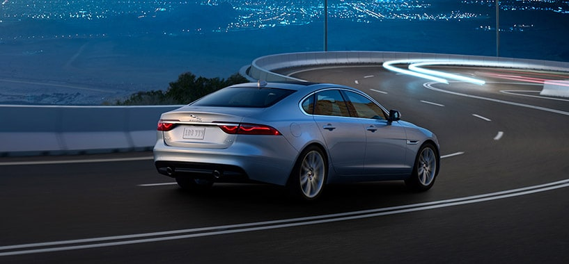 A Silver Jaguar XF Driving On  Winding Road At Night