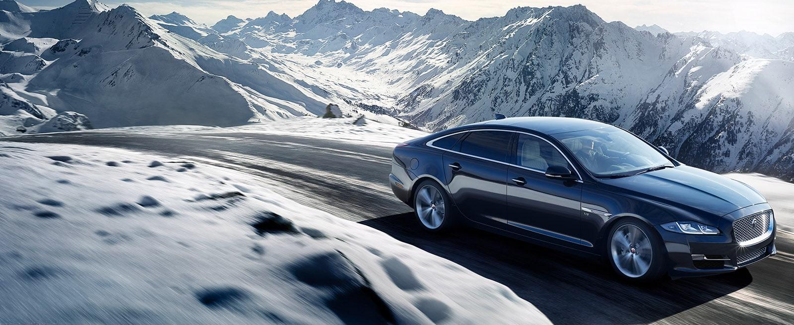 A Black Jaguar XJ Driving Through a Mountain pass